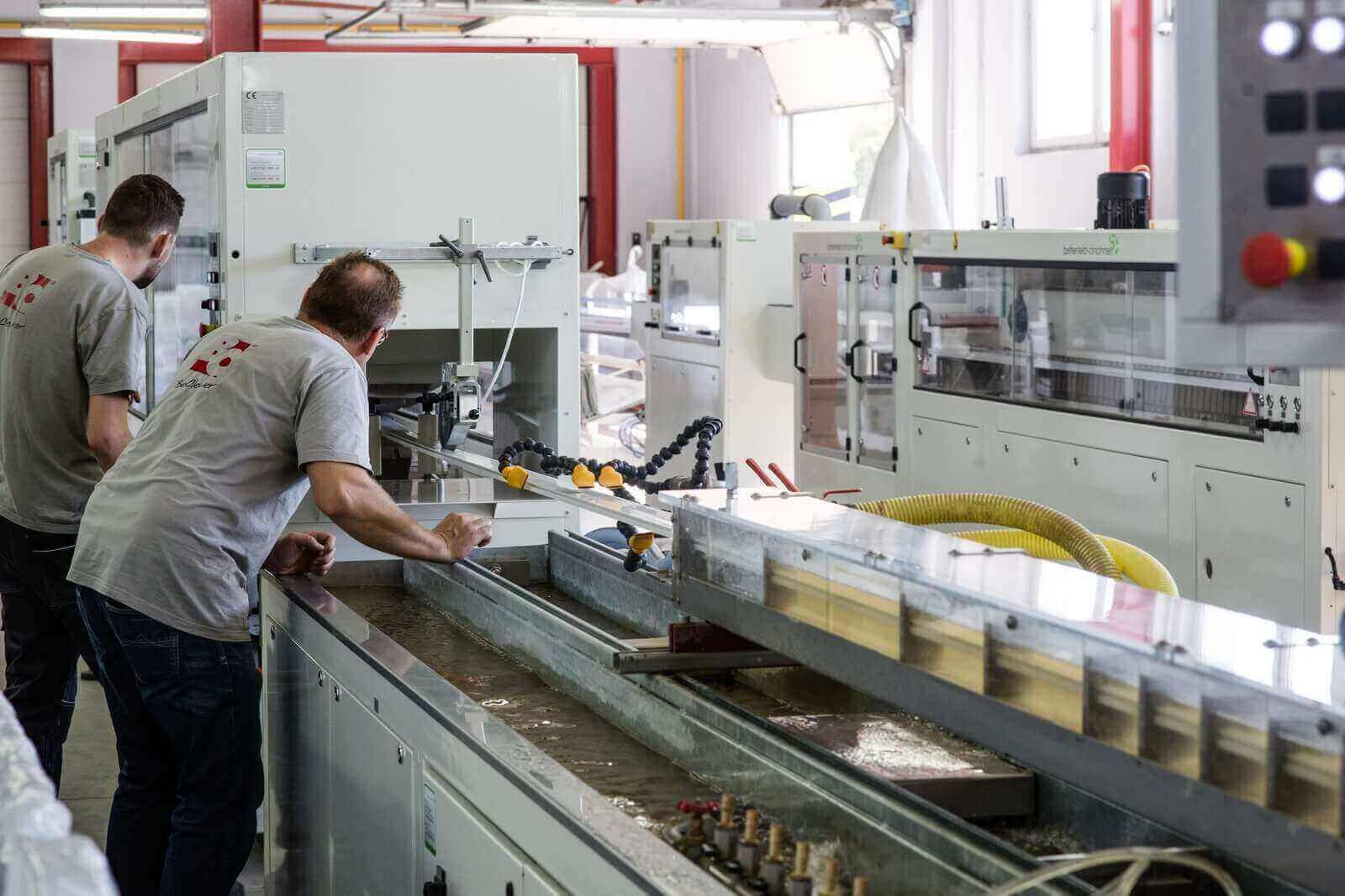 Pracownicy obsługujący maszynę do produkcji profili do skrzynek rolet zewnętrznych, żaluzji zewnętrznychm rolet typu screen.