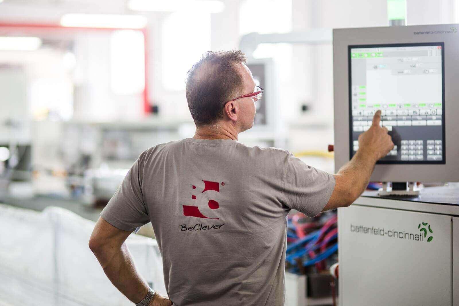 Pracownik obsługujący panel sterujący maszyny do produkcji skrzynek rolet zewnętrznych
