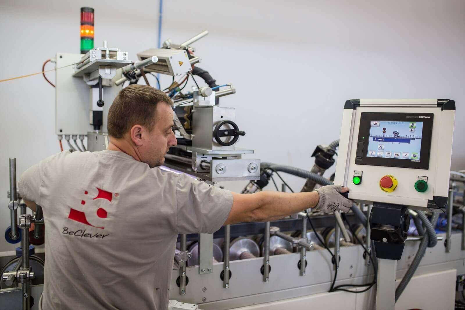 Pracownik obsługujący maszynę do nakładania okleiny