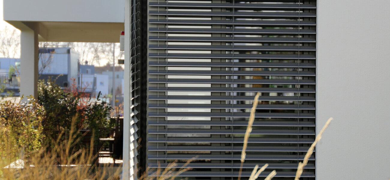 """Nowoczesne żaluzje zewnętrzne. Skrzynka żaluzji fasadowej wykonana z wysokiej jakości tworzywa PVC przez firmę BeClever. Żaluzje fasadowe w nadstawnym systemie CleverBox z rewizją serwisową znajdującą się od zewnętrznej strony budynku. Żaluzje zamontowane na dużym oknie narożnym. Lamele żaluzji wykonane z aluminium w kształcie litery """"Z"""". Żaluzje fasadowe Z90 mają szerokość 90 cm, a ich kąt nachylenia odbywa się w zakresie 90 stopni. Daje to możliwość całkowitego przesłonienia wnętrza od promieni słonecznych. Wysokiej jakości silnik elektryczny sterowany za pomocą pilota zapewnia płynną zmianę pochyłu lameli oraz zwijanie i opuszczanie osłony. Żaluzje zewnętrzne fasadowe sterowane elektrycznie umożliwiają łatwą i szybką regulację natężenia światła w pomieszczeniu według indywidualnych potrzeb użytkownika."""
